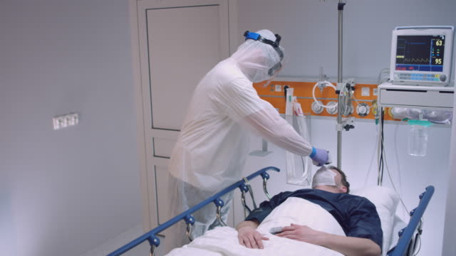 slow motion: nurse in a protective suit measuring coronavirus patient's temperature and consulting with leading doctor - wide shot. shot in 5k r3d - nurse filmów i materiałów b-roll