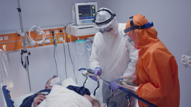 slow motion: nurse in a protective suit measuring coronavirus patient's temperature and consulting with leading doctor - wide shot. shot in 5k r3d - covid ospedale video stock e b–roll