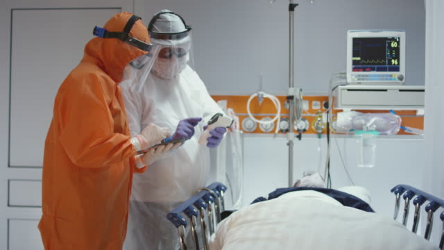 slow motion: nurse in a protective suit measuring coronavirus patient's temperature and consulting with leading doctor - wide dolly shot. shot in 5k r3d - covid ospedale video stock e b–roll