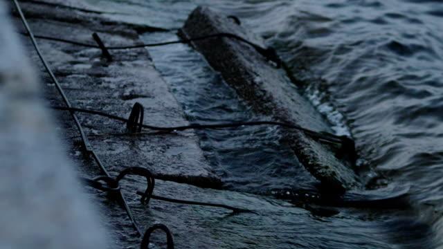 vídeos y material grabado en eventos de stock de cámara lenta de una ola de mar oscuro frío golpeando contra un antiguo rompeolas de hormigón a altas horas de la noche - embarcadero