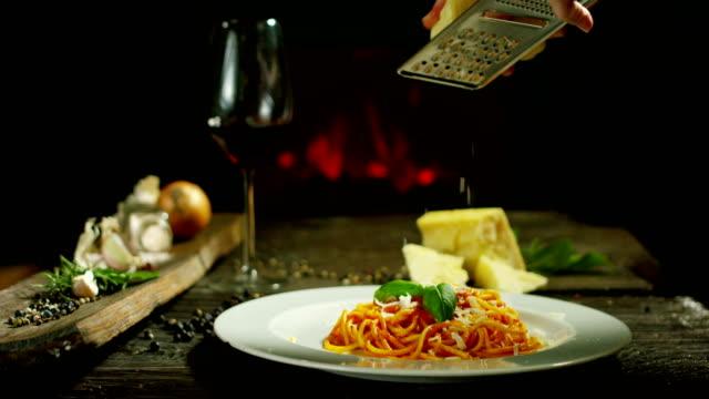 vidéos et rushes de le mouvement lent d'un cuisinier râpe fromage parmesan, fromage italien typique, sur la plaque juste fraîchement infusée. - parmesan