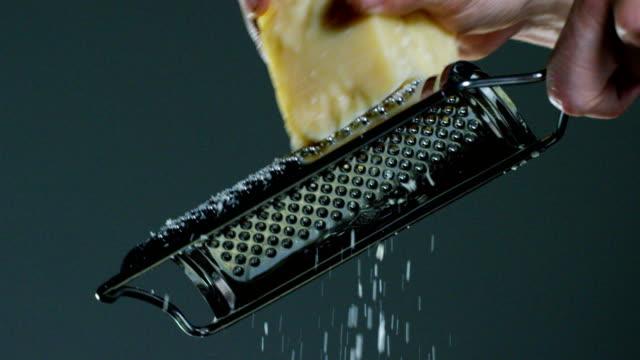 쿡 강판 파머산 치즈의 슬로우 모션, 갓 양조 그냥 접시에 전형적인 이탈리아 치즈. - 치즈 스톡 비디오 및 b-롤 화면