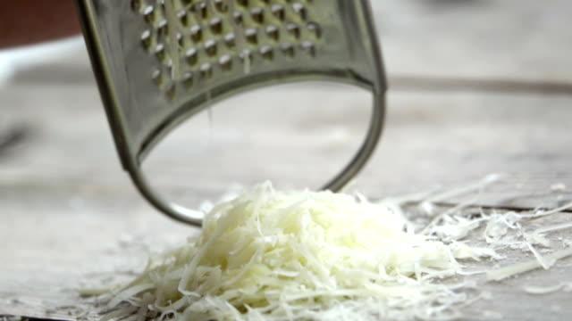 vidéos et rushes de slow motion d'un cuisinier râpe fromage parmesan, fromage italien typique, sur la plaque juste fraîchement brassée. - parmesan