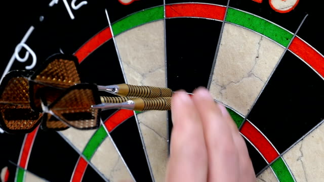 Slow motion of a darts player's hand picking up three darts in triple twenty video