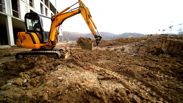 slow motion of a digger digging a pit and throwing dirt. close-up of a excavator bucket that throws out the earth. shot by wide angle lens - azionare video stock e b–roll