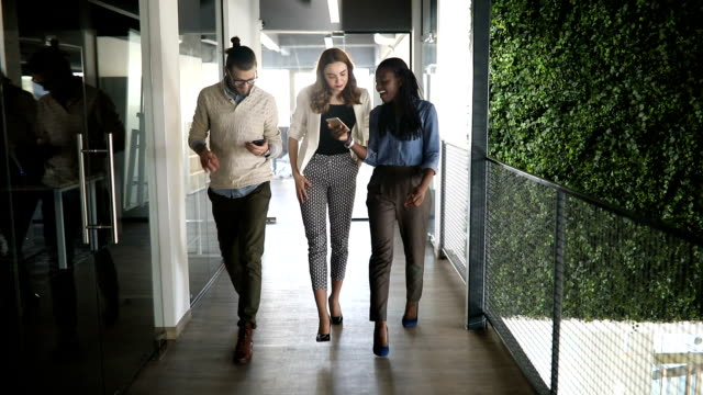 slow motion of a group of people walking in office - collaboration stock videos & royalty-free footage
