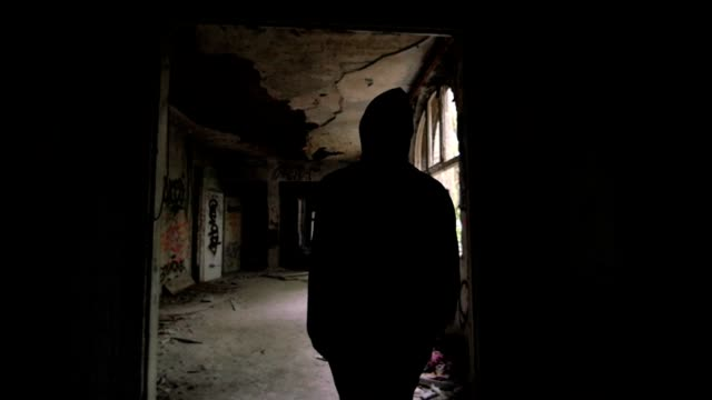 Slow motion of a guy with hood walking through a building video
