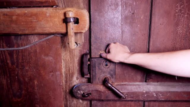 Slow motion of a hand opening an ancient wooden door