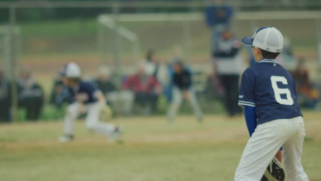 Slow motion of a kid on the field during a baseball game video