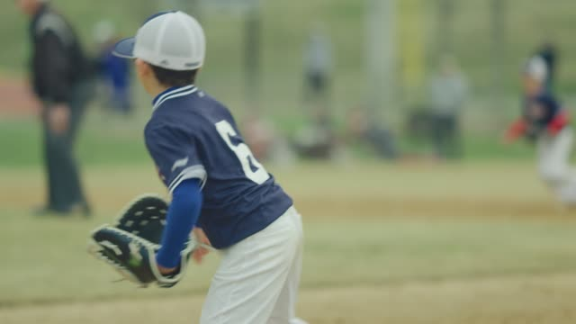 Slow motion of a kid running during a baseball game Daytime slow motion shot of a kid in the field running during a baseball game match sport stock videos & royalty-free footage