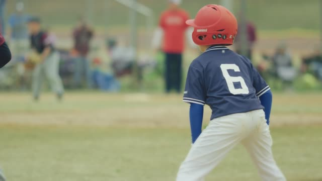 Slow motion of a kid running to second base during a baseball game video