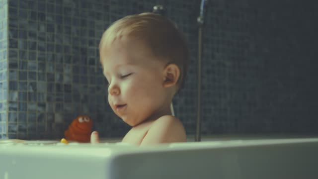 slow motion av en liten söt baby ler och skrattar medan du spelar i badet - baby bathtub bildbanksvideor och videomaterial från bakom kulisserna