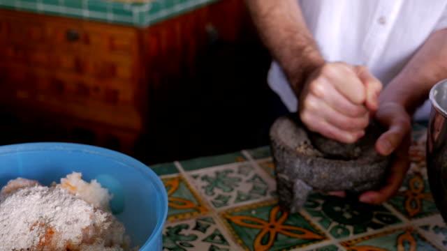 Slow motion of a man grinding pepper in a mortar and pestle video