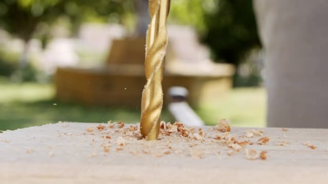 Slow motion of a man using a round saw to cut through wood Close up of a drill making a hole in a piece of wood - slow motion power tool stock videos & royalty-free footage