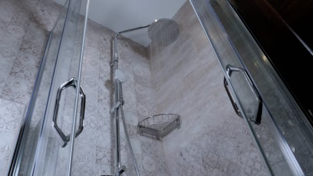 slow motion of a shower that starts running in the bathroom, close up, wide angle view, cleanings, glass shower cabin