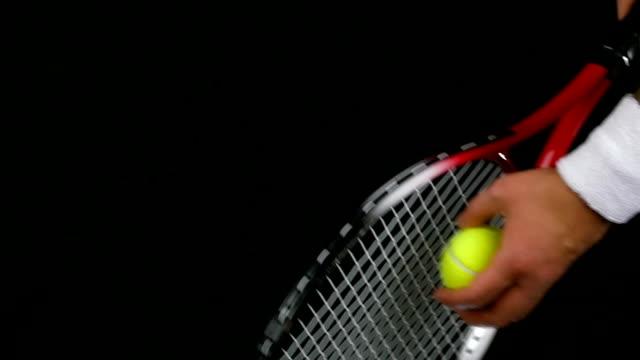 スローモーションのテニスプレーヤーの手を保持、テニスボール、ラケットに向けて、黒色の背景 - テニス点の映像素材/bロール