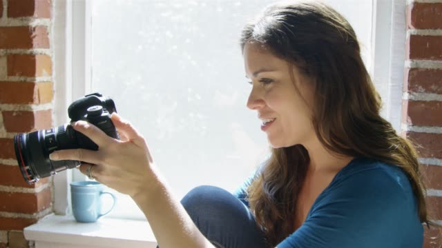 Slow Motion of a woman smiling while checking pictures on her camera video