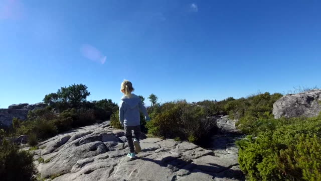 Slow motion of a young boy running along a path A slow motion video of a young boy running along a mountain path table mountain national park stock videos & royalty-free footage