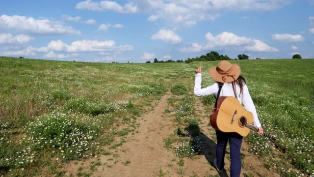 Slow motion of a Young woman with a hat, dressed in white, walking through colourful daisy field full of blossoming flowers at sunset. Hitchhiking