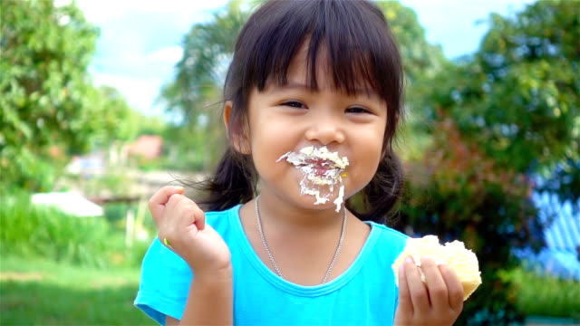 Slow motion of adorable little girl eating cake with her hands video