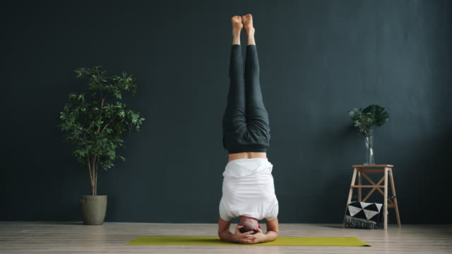 slow motion of advanced yoga student doing headstand working out in studio - posizione corretta video stock e b–roll