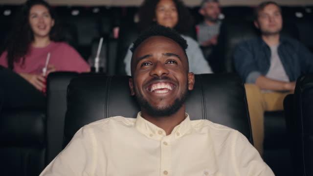 Slow motion of African American man enjoying film in cinema laughing smiling