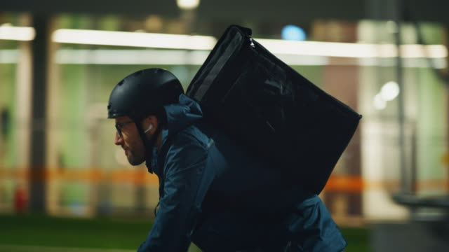 Slow motion of an young delivery courier with bicycle is touching a futuristic screen with augmented reality hologram maps to view the addresses of customers in the evening in a city center