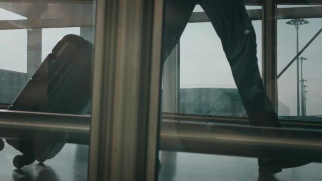 slow motion av en ung elegant affärsman i kostym går med en resväska på den internationella flygplatsen med ett solsken från fönstret. - affärsresa bildbanksvideor och videomaterial från bakom kulisserna