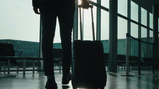 stockvideo's en b-roll-footage met de langzame motie van een jonge elegante zakenman in een kostuum loopt met een koffer in de internationale luchthaven met een zonneschijn van het venster. - zakenreis