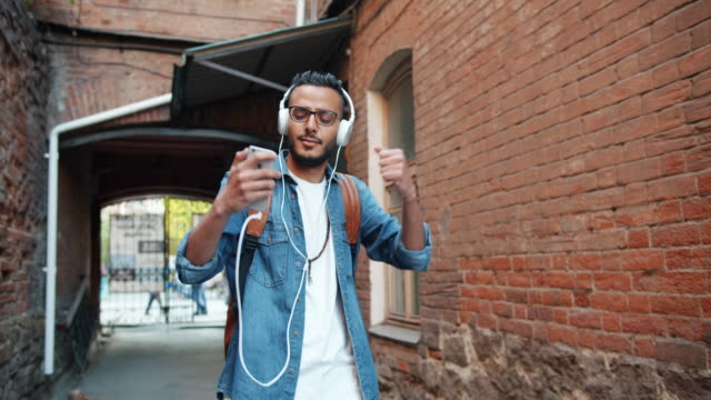 Slow motion of Arab listening to music outdoors with smartphone and headphones