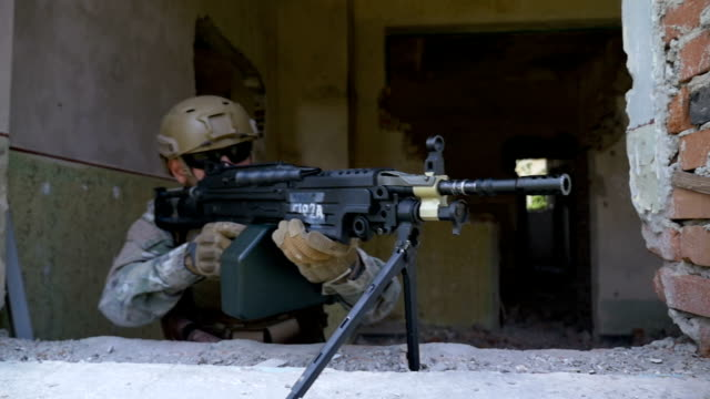 Slow motion of armed soldier in camouflage with machine gun rifle looking out the window video