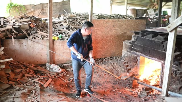 slow motion of Asian Chinese man is fire up kiln drying the pottery with tradition oven