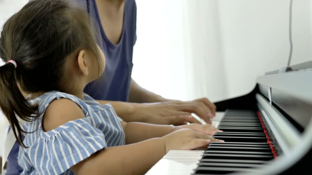 4k : slow motion of asian girl playing piano with her mother - piano filmów i materiałów b-roll