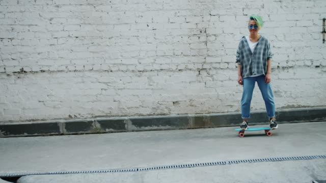 vídeos y material grabado en eventos de stock de cámara lenta del hipster asiático patinando al aire libre mostrando pulgares hacia arriba - moda hipster