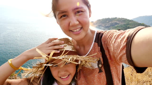 Slow motion of Asian mother and daughter taking selfie photograph together video