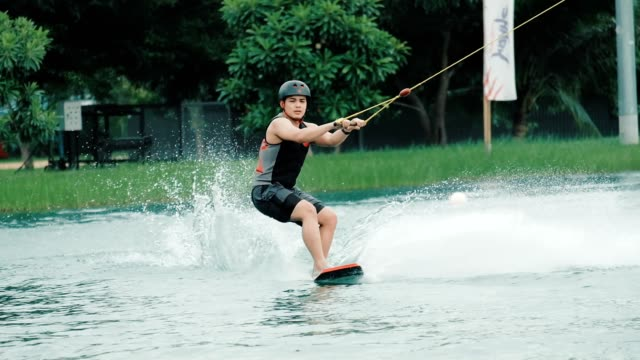 Slow motion of Asian Young Man Enjoys Cable Wakeboarding Slow motion of Asian Young Man Enjoys Cable Wakeboarding young singles stock videos & royalty-free footage