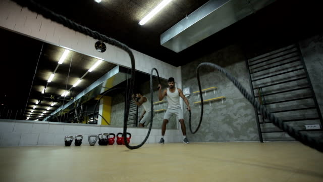 Slow motion of athletic black man doing battle ropes exercise in a gym. video