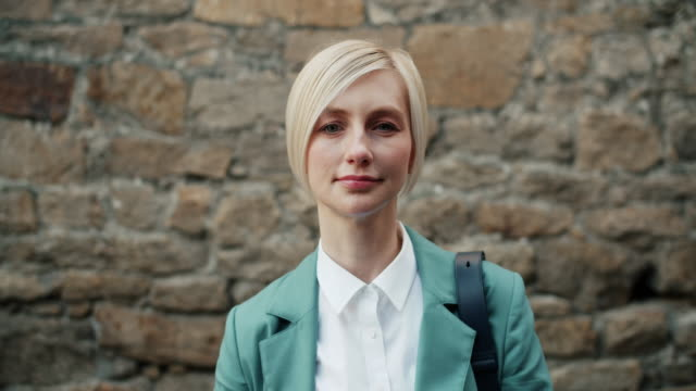 Slow motion of attractive businesswoman standing outdoors with serious face Slow motion portrait of attractive businesswoman standing outdoors with serious face looking at camera with brick wall in background. Youth and city concept. real life stock videos & royalty-free footage