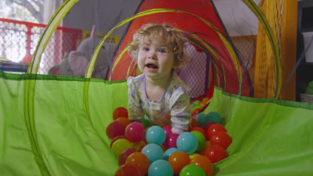 Slow motion of baby girl crawling inside a ball pit video