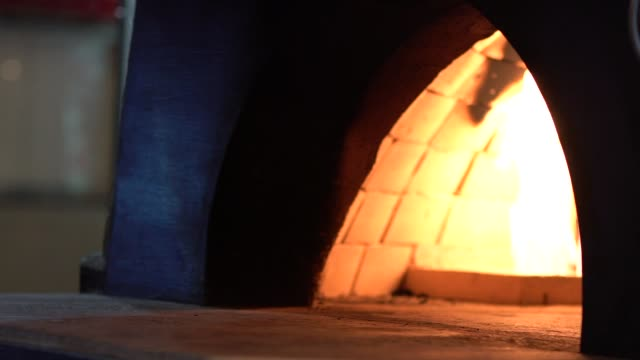 Slow motion of Baking traditional italian pizza in wood fired stone oven.