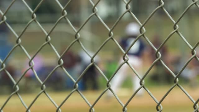 Slow motion of baseball game seen from behind a fence video