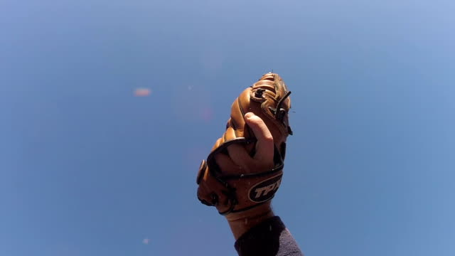 slow motion of baseball hitting dirt out of baseball glove - ловить стоковые видео и кадры b-roll