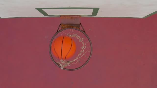 vídeos y material grabado en eventos de stock de cámara lenta del baloncesto pasando a través de un aro en una cancha al aire libre - basketball hoop
