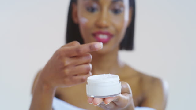 Slow motion of beautiful african woman with perfect skin just cleaned from impurities gently applying on face with fingers day or night cream with jar in focus Slow motion of beautiful african woman with perfect skin just cleaned from impurities gently applying on face with fingers day or night cream with jar in focus. serum sample stock videos & royalty-free footage