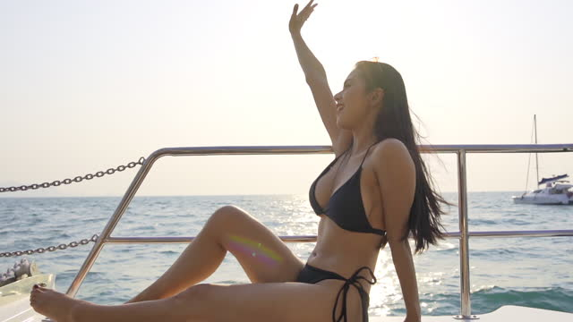 Slow motion of Beautiful Asian woman in bikini and sunglasses relaxing on sailing yacht at summer sunset. Smiling sensual girl enjoy and having fun with luxury outdoor lifestyle in summer holiday vacation.