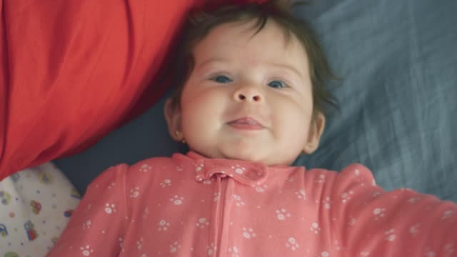 Slow motion of beautiful baby looking at camera video