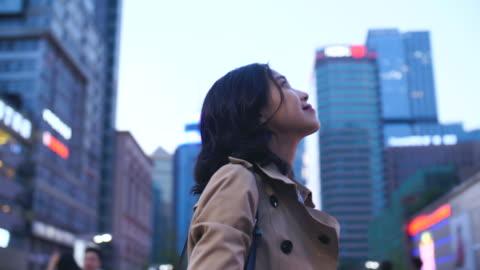 yavaş hareket cityscape şehrin yukarı isteyen güzel çinli kadın - abd dışı yer stok videoları ve detay görüntü çekimi