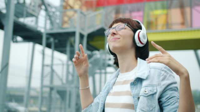 Slow motion of beautiful girl in headphones dancing outdoors having fun