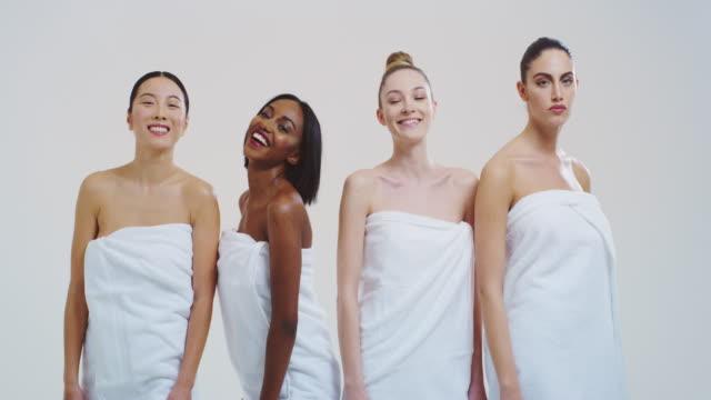 zeitlupe von schönen jungen lächelnden frauen verschiedener ethnien mit perfektem festen und schlanken körper in weißen badetüchern tanzen und spaß isoliert auf weißem hintergrund - kosmetische behandlung stock-videos und b-roll-filmmaterial