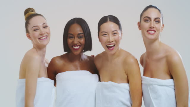 Slow motion of beautiful young women of different ethnicities with perfect firm and slim body in white bathing towels having fun and laughing in camera isolated on white background Slow motion of beautiful young women of different ethnicities with perfect firm and slim body in white bathing towels having fun and laughing in camera isolated on white background. serum sample stock videos & royalty-free footage